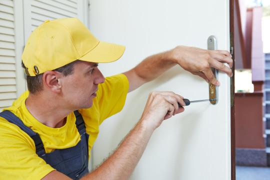 Male handyman carpenter worker at interior wood door lock installation or repairing